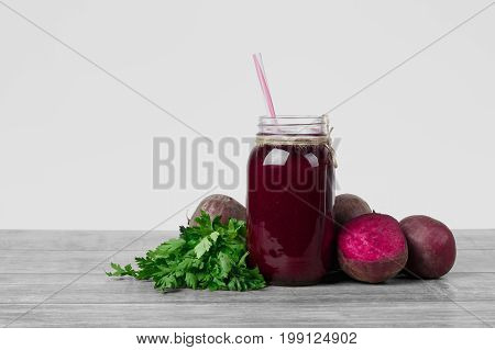 A transparent jar of beet beverage on a gray wooden table isolated on a white background. A set of healthy vegetables and greens. Chopped beetroots and refreshing salads. Copy space