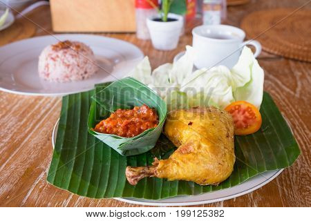 Indonesian char-grilled chicken on a plate with banana leaf. Served steamed rice fresh green vegetables and red chili paste.