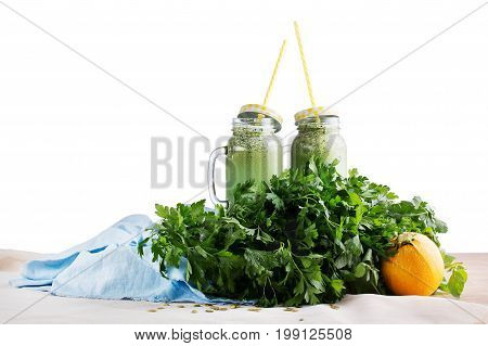 Two big mason jars full of healthful green smoothies on a blue fabric, isolated on a white background. Smoothies from celery, parsley, spinach, and cucumber. A zucchini and branches parsley on a desk.
