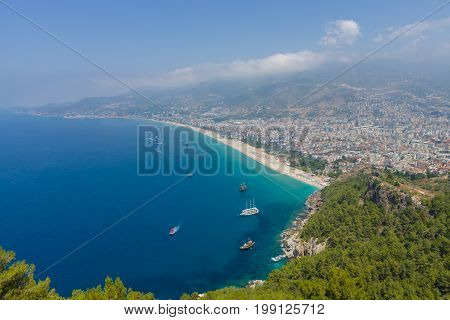 ALANYA TURKEY - JULY 09 2015: The city beach in Alanya. The coastline is receding into the distance. The view from the bird's eye view. Alanya - a popular holiday destination for European tourists.