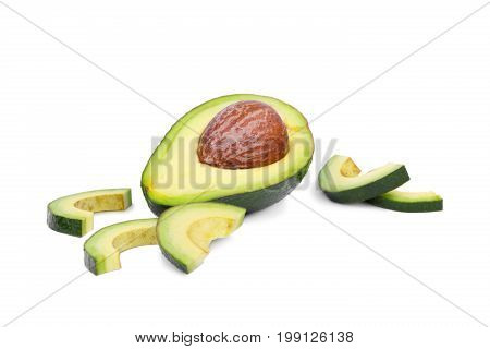 A fresh and organic green avocado cut in half with a large stone and a rough leathery skin, isolated on a white background. A few slices of fruit near the healthful avocado. Copy space.