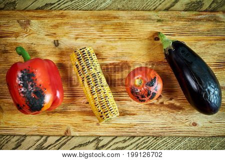 Vegetables fried on a grill and stacked on a cutting board