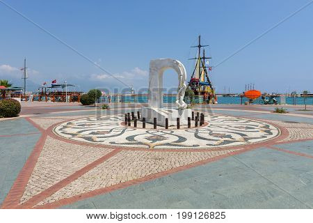 ALANYA TURKEY - JULY 09 2015: Monument and pleasure boats in the sea port of Alanya. Alanya - a popular holiday destination for European tourists.
