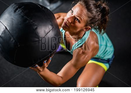 Woman athlete exercising with medicine ball, toned image