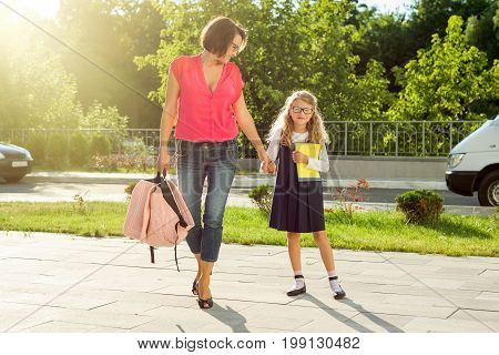 Mom and schoolgirl of primary school holding hands. The parent takes the child to school. Outdoors return to the concept of the school