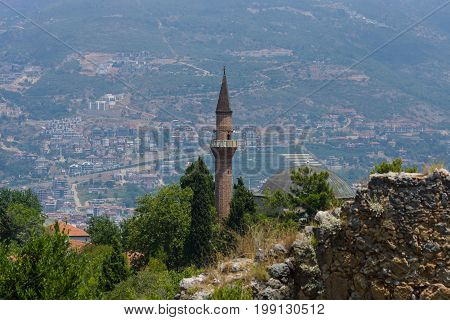 Minaret in the background rooftops central Alanya and the Taurus Mountains. Turkey.