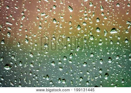 Raindrops on the home window surface against colorful green and yellow background