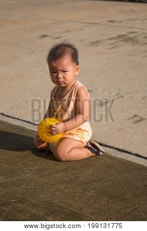 The boy is playing the ball on the street in front of his house.  While playing, fell on the floor.  The boy holds the ball in his hand.
