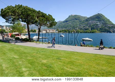 Lugano Switzerland - 5 may 2016: People walking on the lakeside of Lugano on the italian part of Switzerland