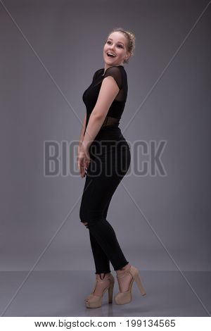 blonde girl embarrassed dressed in black on gray background