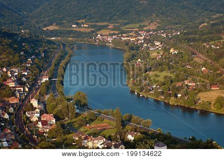 European river Elbe in Dolni Zalezly and Sebuzi villages when viewed from Mlynaruv kamen lookout in czech central mountains tourist area at sommer sunset