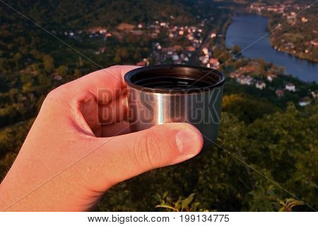 Sipping espresso from thermos over valley of european river Elbe when viewes from Mlynaruv kamen lookout in czech central mountains tourist area at sommer sunset