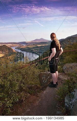 Mlynaruv kamen Czech republic - July 08 2017: tourist is looking from lookout to valley of european river Elbe in czech central mountains tourist area at sommer sunset