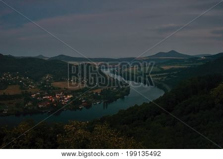 European river Elbe in Cirkvice village when viewed from Mlynaruv kamen lookout in czech central mountains tourist area at sommer night