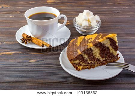 A tasty cake and a cup of coffee. A bowel with sugar cubes and cinnamon sticks on a small plate near the coffee and a fork on dark wooden background