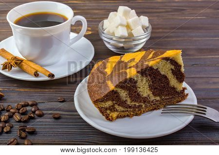 Delicious cake on a plate with a fork. White cup with black coffee and cinnamon sticks near it. Coffee beans and a bowel with sugar cubes on dark wooden table