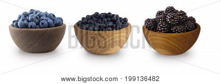 Black-blue berries isolated on white background. Collage of berries. Blueberry bilberry blackberries. Collection of fruits and berries in a bowl.