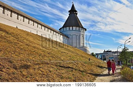 Against the background of the blue sky and cirrus clouds - a panorama of the wall and the corner tower of the fortress. This is the Astrakhan Kremlin an architectural monument of the 16th-18th centuries. Downstairs mother and son follow the path. Away a g