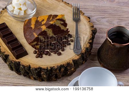 A coffee cup with a piece of cake on wooden stump a chocolate bar fork coffee beans and bowl with sugar cubes on a wooden table