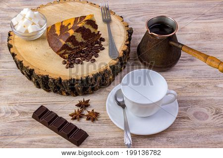 Top view of a piece of chocolate cake on wooden stump with a coffee cup tea spoon fork anise coffee beans chocolate bar and bowl with sugar cubes on a bright wooden background
