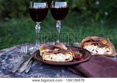 Strudel with cheese and sun-dried tomatoes. The table is set for dinner. Lunch. Homemade pie strudel and snacks vegetables fruits cheese.