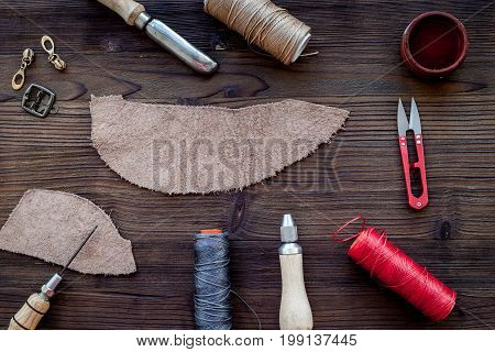 Leather craft accessories. Tools and matherials on dark wooden table background top view.