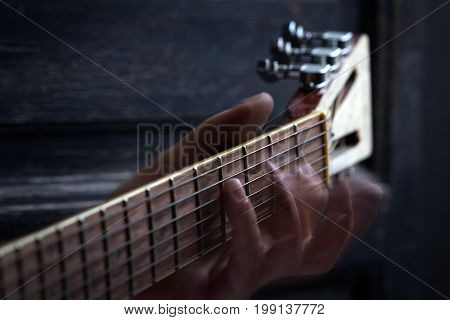 fingers playing acoustic guitar on black dark wooden background with selective focus and motion blur
