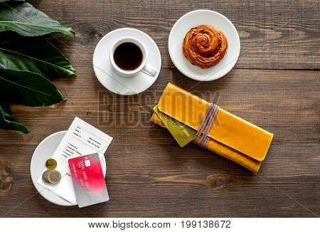 Pay bill at cafe by card. Purse, bill and bank card near coffee and bakery on dark wooden table top view.