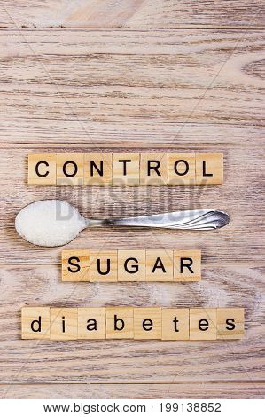 Diabetes control block wooden letters and sugar pile on a spoon