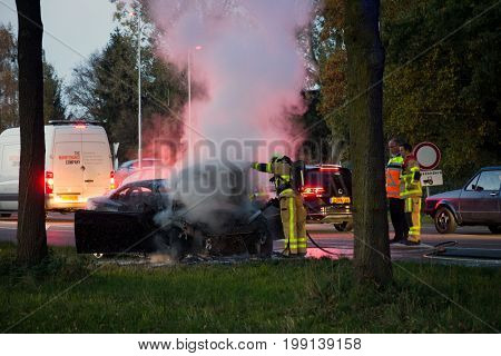 ACHTERHOEK NETHERLANDS - OCT 29 2015: Firefighters near a burned out car wreck.
