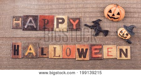 Happy halloween text with halloween decorations on a wood background