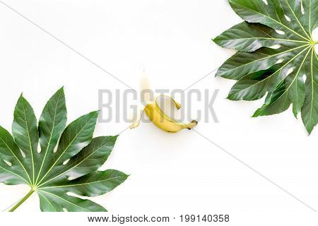 Tropical concept. Lush leaves and ripe bananas on white background top view.