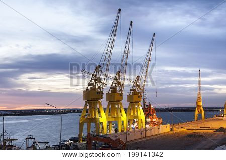 Yellow cranes in the old port of Huelva illuminated at night. Andalusia Spain