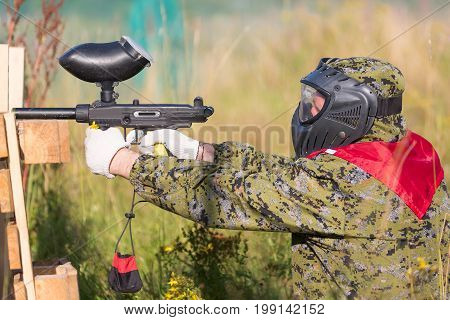 Paintball sport player in protective uniform and mask playing and shooting with gun outdoors