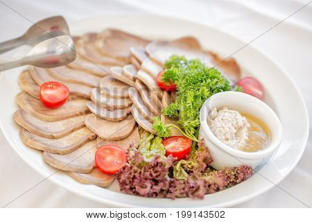 Meat plate with delicious pieces of sliced ham, sausage, meat, tomatoes, horseradish, parskey with herbs and spoon. Close up with selective focus