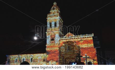 Quito, Pichincha / Ecuador - August 9 2017: Crowd admiring the spectacle of lights projected on the facade of the Church of Santo Domingo, in the historical center of Quito. Fiesta de la Luz is an event that takes place in Quito every August