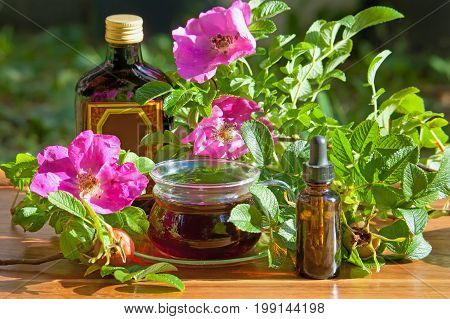 Healthy tea cosmetic oil and tincture bottle of dogrose berries on wooden table. Herbal medicine.