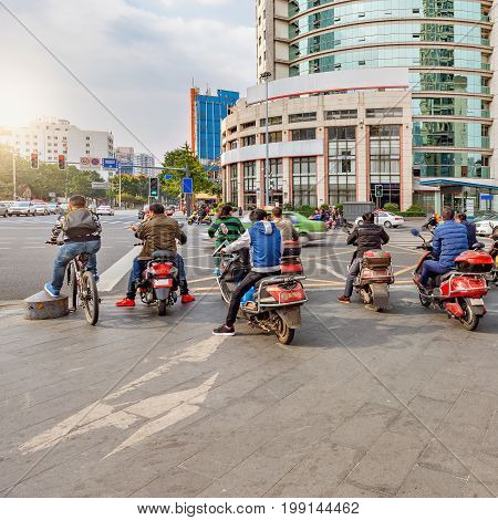 People on the motorbikes wait by the crossroad. Chengdu. China.