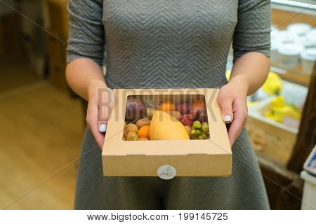Box with cherries in a female hand, on a background of a garden