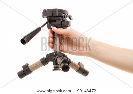 Small tripod in a female hand on a white background isolation