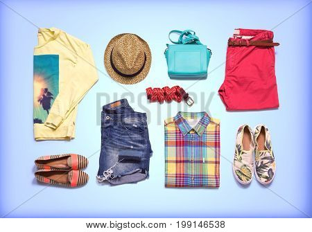 Clothes and accessories. Collection of summer clothes. Colorful folded clothes on blue background