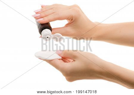 Tonic for the face with a cotton disc in the female hand on a white background isolation