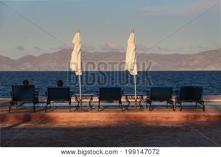 Two silhouetted people sitting in deck chairs looking across the Sea of Cortez at Rancho las Cruces, Baja, Mexico