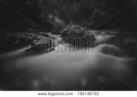 A mountain river flowing thorough stones, among the mountains of Carpathians, Romania, Transylvania.Photo in black and white with a long exposure, the effect of water movement, blurred.