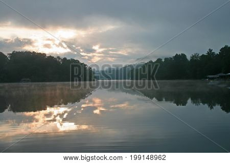the sun rises on a cloudy day over Lake Chatuge
