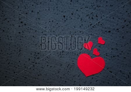 Symbol of love and valentines day background - bright red hearts on a black background. Place for writing text. Love concept