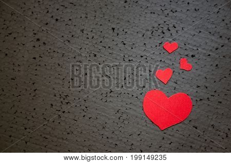 Beautiful bright red heart on a rough black background. A symbol of love and valentines day batsground. Copy Space