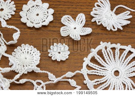 Wooden background with cotton crochet lace white flowers
