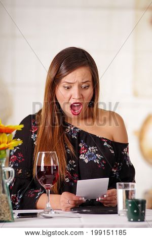 Portrait of surprised woman with a bill in her hand, after the dinner, in a blurred background.