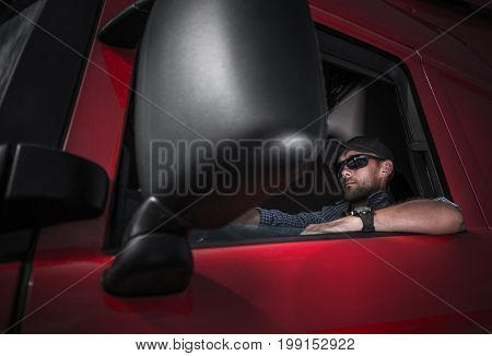 Truck Driver Job. Caucasian Driver in His Brand New Red Semi Truck Tractor.